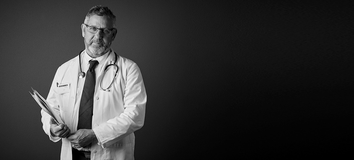 Studio portrait of a handsome mature male doctor holding medical records while standing against a dark background
